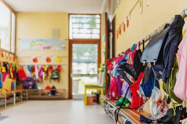 Image d'un couloir d'école avec les sacs et vêtements des enfants.